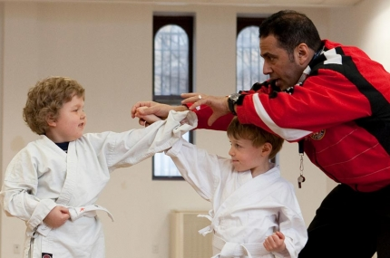 Two boys doing karate moves with instructor at YMCA studio