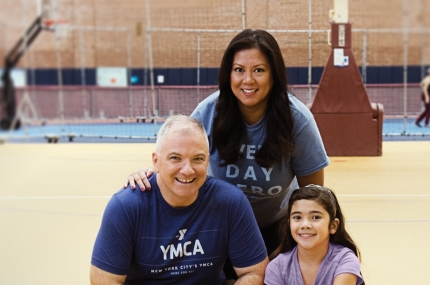 Family playing in gym together with basketball at YMCA