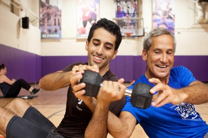 Two adult men passing weight to each other in YMCA fitness class in indoor gymnasium in Brooklyn