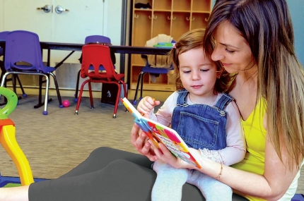 Mom reading to baby at YMCA reading room