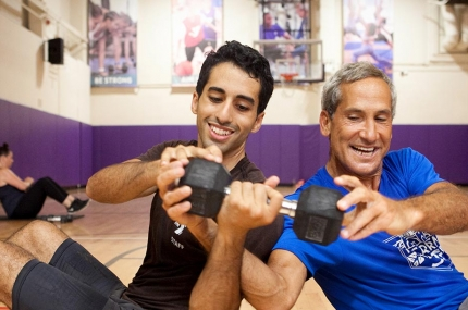 Two adult men passing weight to each other during fitness class in YMCA gym in Brooklyn