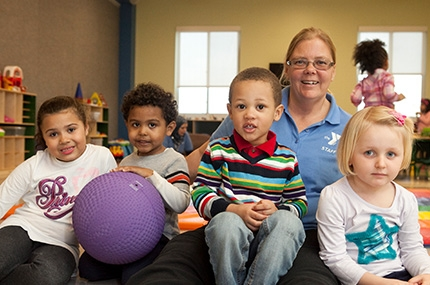 YMCA staff member sitting on floor of child playroom with four kids and purple ball