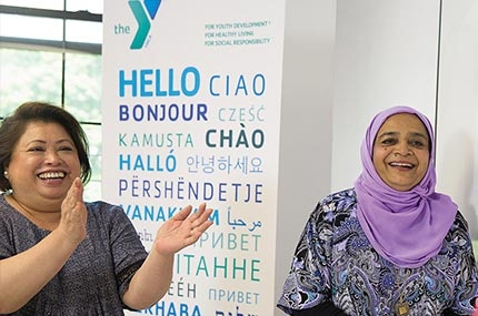 Two women smiling in Flushing YMCA new americans welcome center english classroom