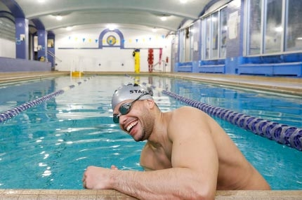 Man with cap and goggles smiling as he starts to swim at North Brooklyn YMCA's indoor pool