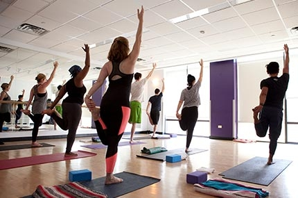 Yoga class with mats and arms up in Brooklyn YMCA fitness studio