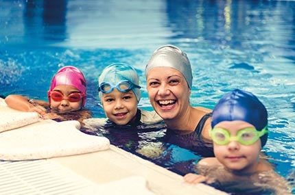 Woman and three kids wearing caps and googles smiling and swimming in pool