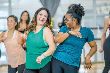 Two women smiling and bumping hips in group fitness dance class