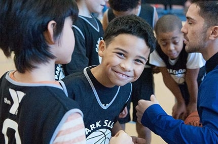 Boy in basketball team huddle at Park Slope Armory YMCA in Brooklyn smiles