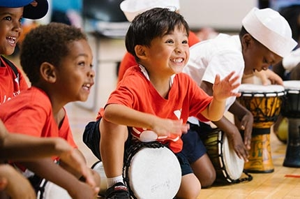Boys smiling and playing drums at Bronx YMCA summer camp