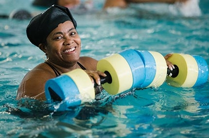 Woman smiling in Bronx YMCA indoor pool during water aerobics class