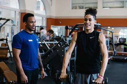 Teen lifts weights with personal trainer at Ridgewood YMCA strength training center in Queens