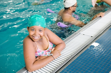 Girl smiles on side of Castle Hill YMCA indoor swimming pool