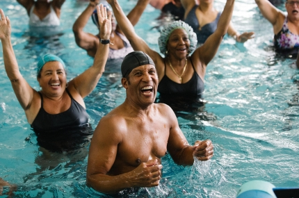 Class smiling during aqua aerobics class at Bronx YMCA indoor pool