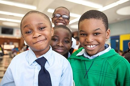 Group of boys smiling at YMCA afterschool program in NYC elementary school
