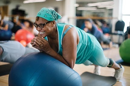 Woman with aqua bandana smiles while doing core exercises during Rockaway YMCA pilates mat class