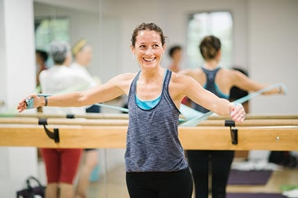 Woman using elastic band in YMCA barre class