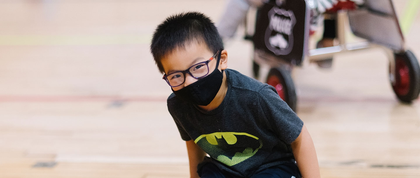 A boy wearing a mask smiles at the camera.