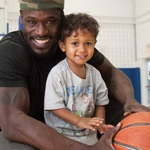 Man holding basketball and toddler son and smiling in YMCA indoor gymnasium