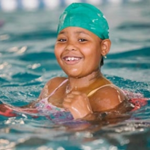 Young girl smiles while swimming in YMCA indoor pool in Castle Hill, Bronx