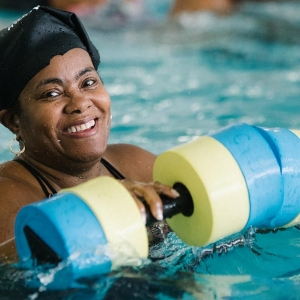 Woman with foam water weights during aqua aerobics class at Bronx YMCA indoor pool