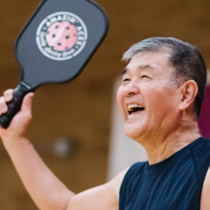 Man smiling with pickleball paddle