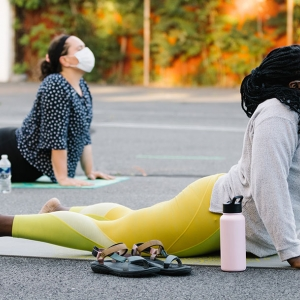 Two women participate in an outdoor yoga class at the YMCA.