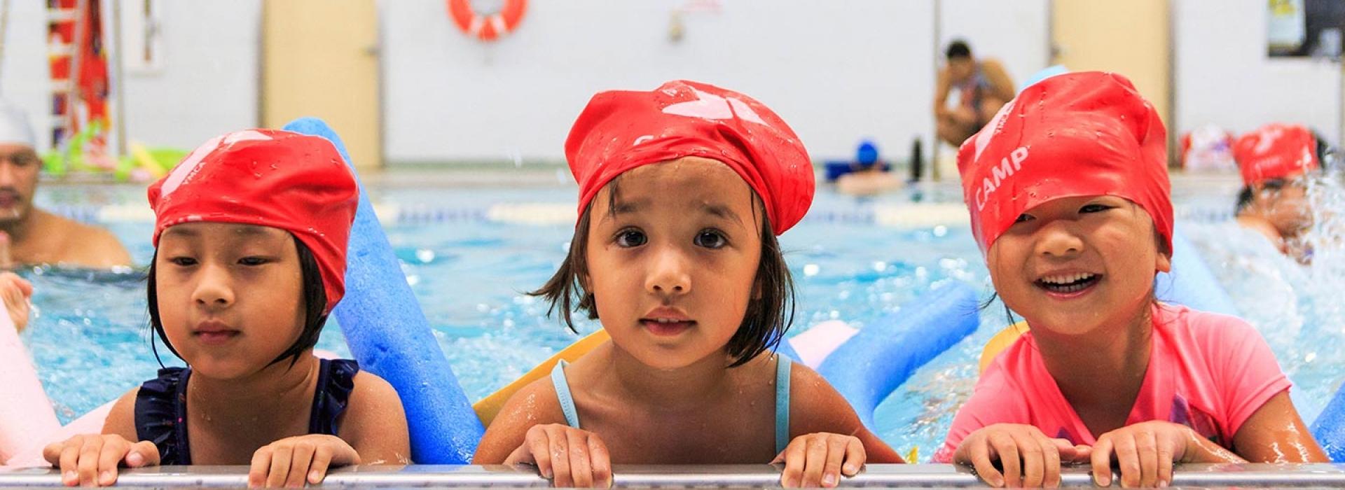 08358b801 Three girls swimming in Long Island City YMCA pool during summer camp