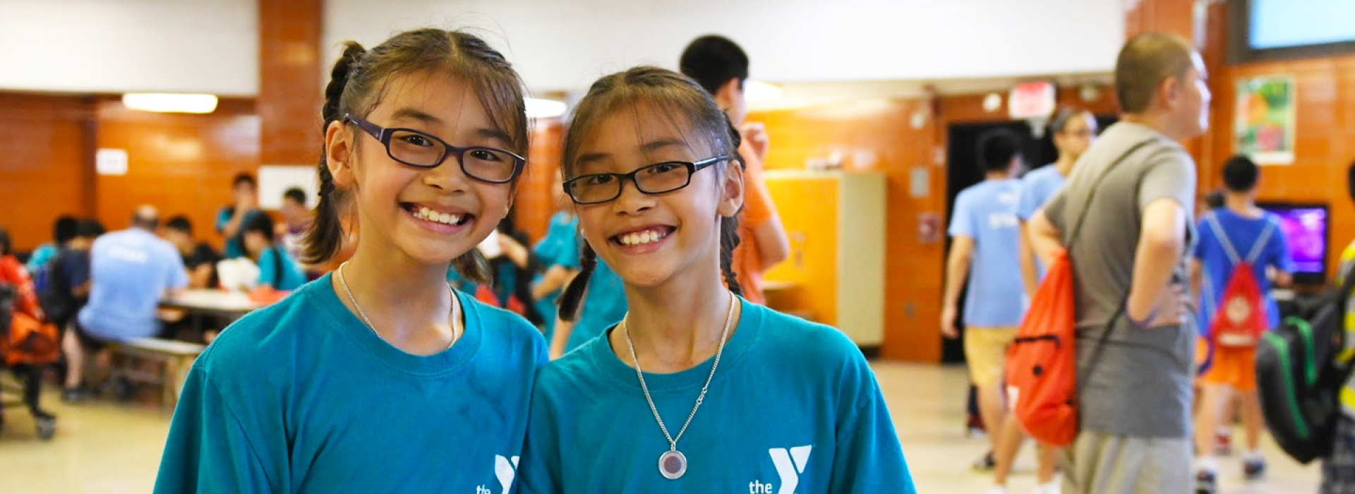86766a814 Two girls in glasses smile from the Chinatown YMCA Summer Day Camp.